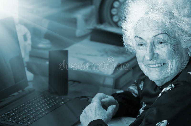 La nonna felice si siede al computer immagini stock libere da diritti