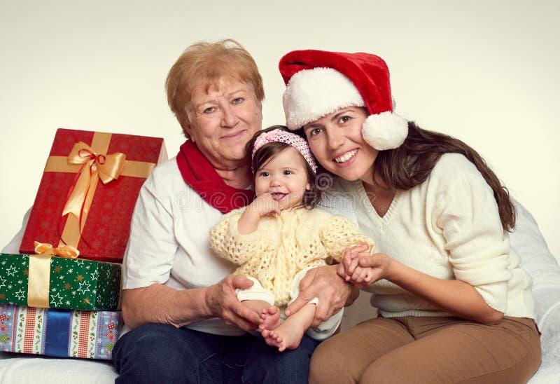 La nonna, il derivato e la nipote si sono vestiti in Santa che il cappello con i contenitori di regalo si siede sul sofà, fondo b fotografie stock