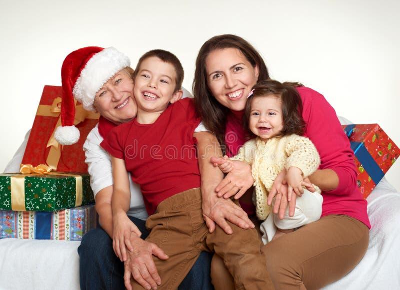 La nonna, il derivato ed il nipote si sono vestiti in Santa che il cappello con i contenitori di regalo si siede sul sofà, fondo  immagini stock