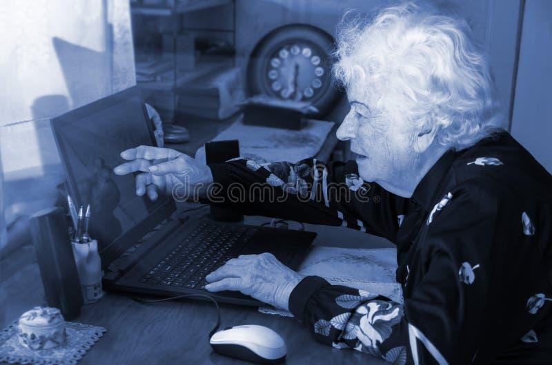 La nonna impara lavorare a casa sul computer fotografia stock