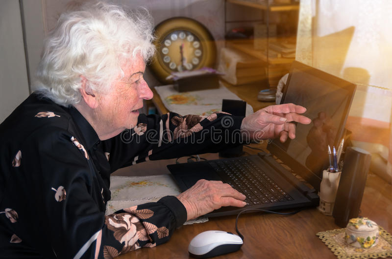 La nonna impara lavorare a casa sul computer fotografie stock libere da diritti
