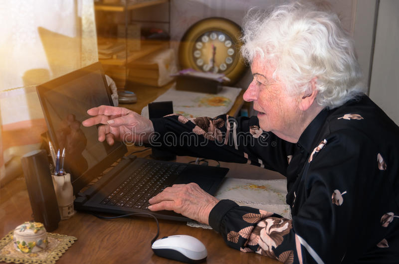 La nonna impara lavorare a casa sul computer immagini stock