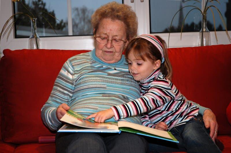 La nonna legge un libro con la sua piccola nipote fotografia stock libera da diritti