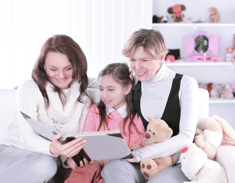 La nonna, la madre e la figlia hanno letto un libro interessante, sedentesi sullo strato Foto con lo spazio della copia fotografie stock libere da diritti