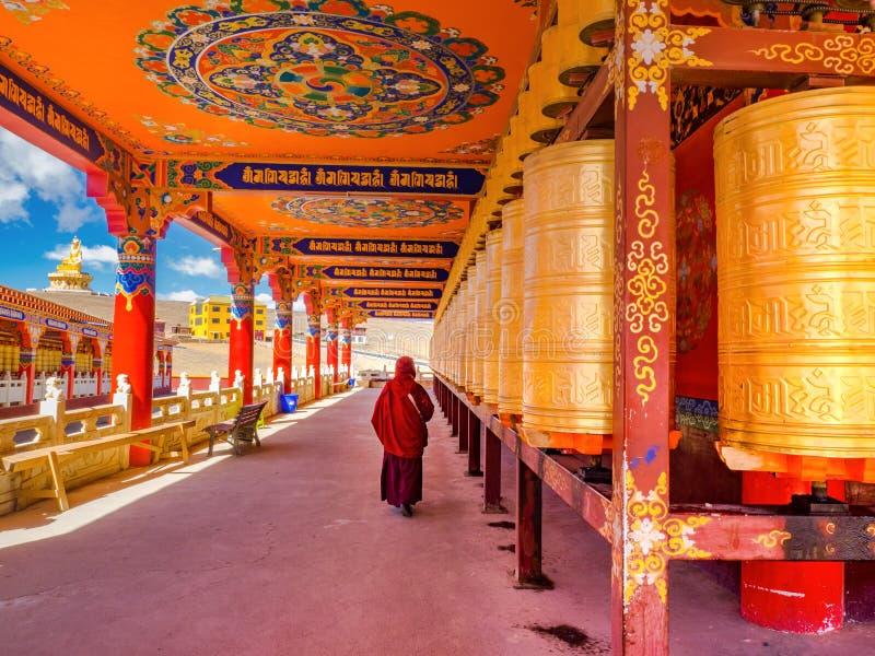 La nonne bouddhiste marchant à la prière roule en Yarchen Gar Monastery photos libres de droits