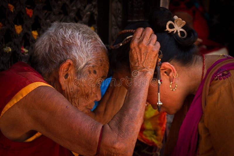 La nonne bouddhiste tibétaine donne une bénédiction dans Boudhanath, Katmandou, images stock