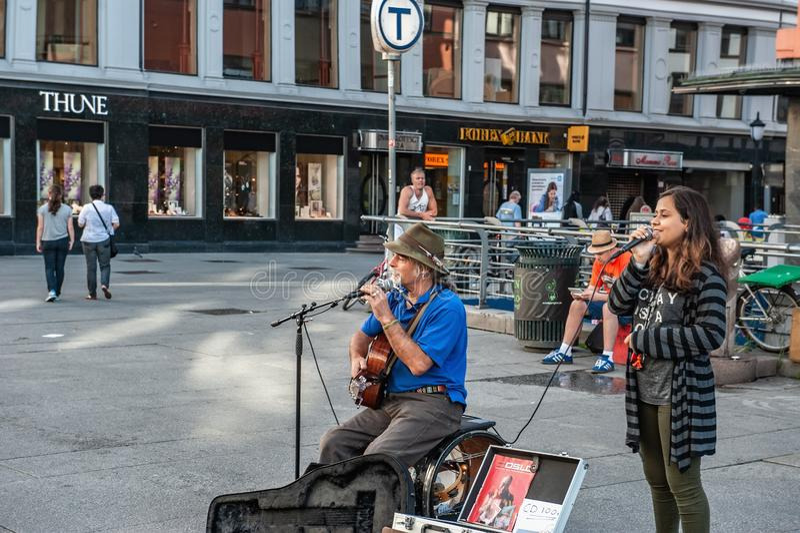 La Norvegia, Oslo 1? agosto 2013 Musicista e ragazza che cantano nel quadrato a Oslo, la capitale della Norvegia Reddito extra pe fotografia stock