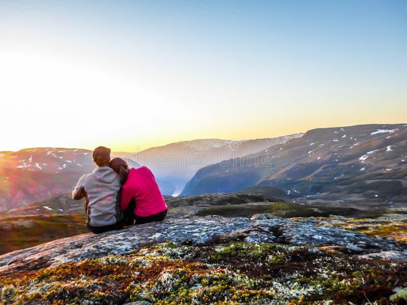 La Norvegia - una coppia che si siede sulla roccia e che guarda il tramonto fotografia stock