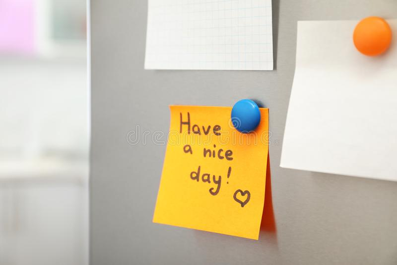 """La nota con testo """"ha un giorno piacevole """"e strati vuoti sulla porta del frigorifero in cucina fotografia stock"""