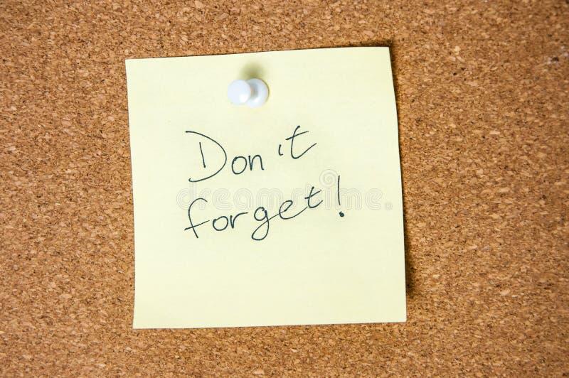 La nota de papel escrita con el ` t de Don olvida la inscripción en tablero del corcho imagen de archivo