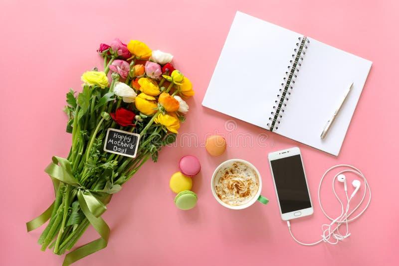 La nota felice del giorno del ` s della madre sul ranuncolo fiorisce, tazza di cappuccino, makarons agglutina, cellulare con le c immagini stock