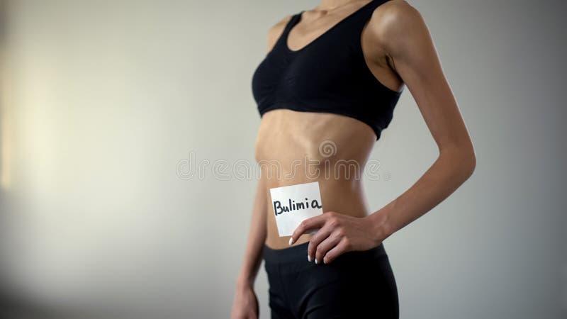 La nota scarna di bulimia della tenuta della ragazza, corpo esaurito ha bisogno dell'aiuto, disordine alimentare fotografia stock libera da diritti