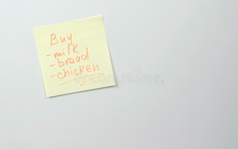 La nota sobre el papel amarillo de la etiqueta engomada cubre con la lista de palabras de pollo de la leche del pan de los produc imagen de archivo libre de regalías