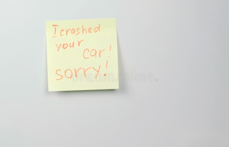 La nota sobre el papel amarillo de la etiqueta engomada cubre con palabras que estrellé su coche triste fotos de archivo