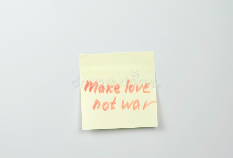 La nota sobre las hojas amarillas del papel de la etiqueta engomada con palabras de la motivación hace guerra del amor no imagenes de archivo