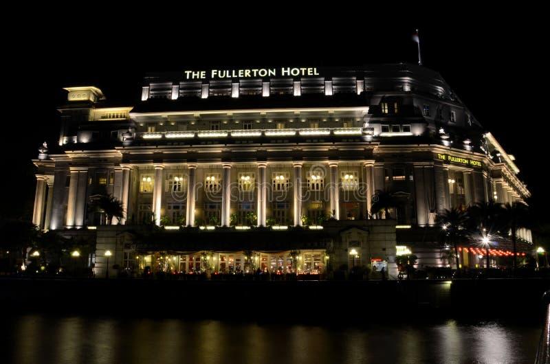 La notte ha sparato della costruzione dell'hotel di Fullerton in barca del fiume di Singapore Quay immagine stock libera da diritti