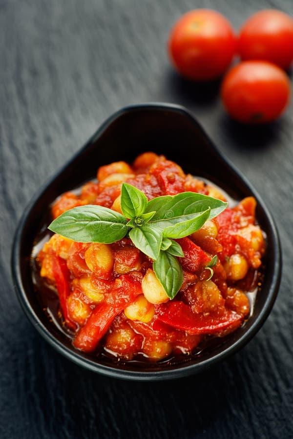 La nourriture de Vegan, pois chiches a cuit avec des tomates et des poivrons images stock