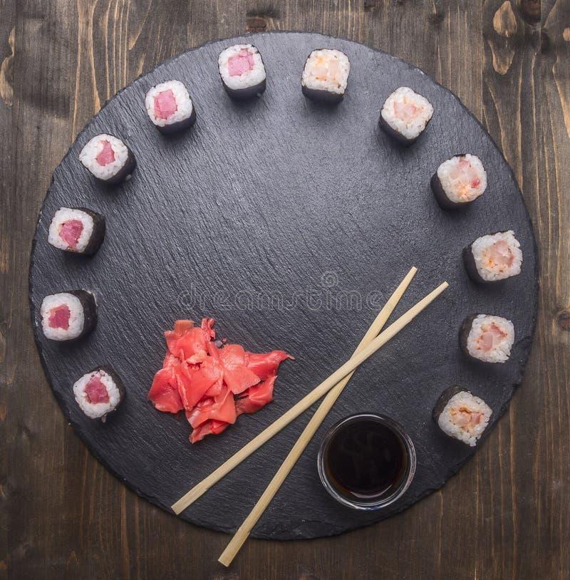 La nourriture japonaise, les sushi avec les saumons et le thon, le gingembre frais, la sauce de soja et les baguettes ont aligné  photo stock