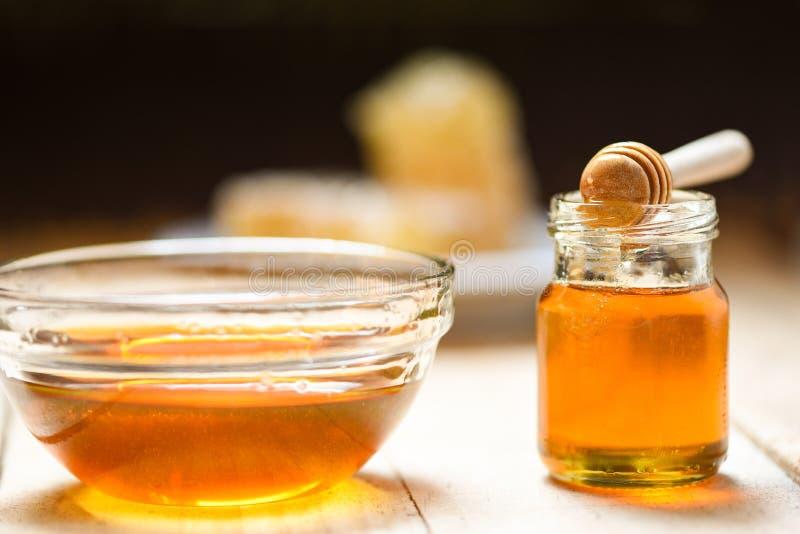 La nourriture saine de miel frais/se ferment du miel doux jaune en verre de cuvette et de pot avec le plongeur en bois photos libres de droits