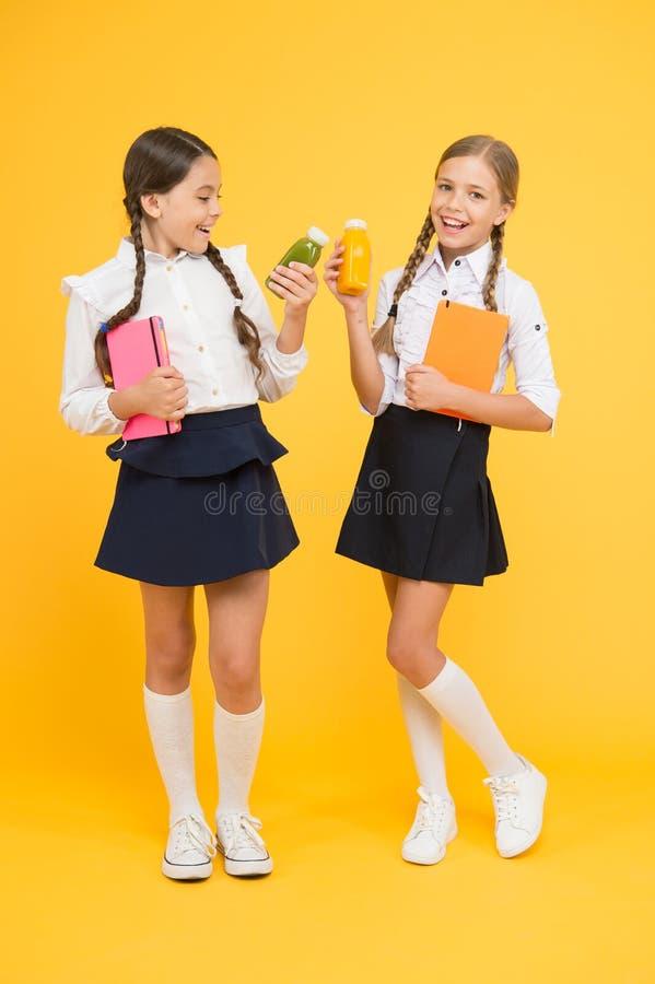 La nourriture saine est la vie saine Les élèves boivent du jus à la bibliothèque Nourriture saine journal intime et laiterie Temp images stock