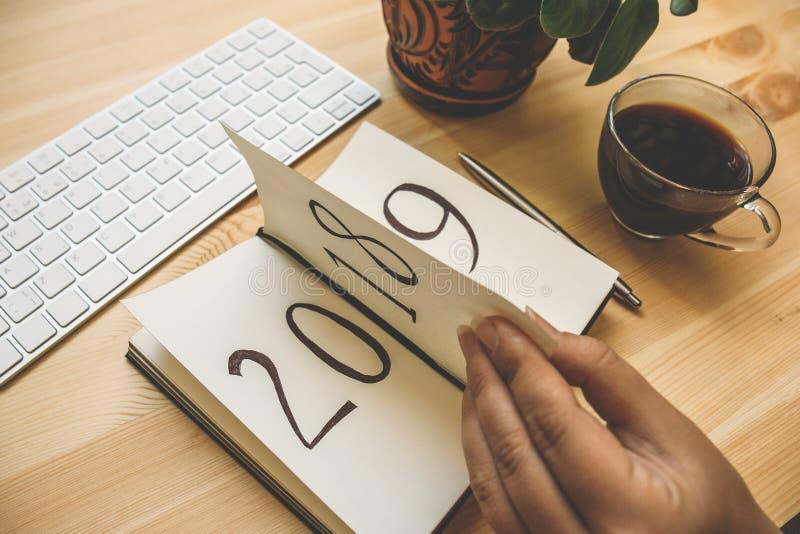 La nouvelle année 2019 est prochain concept La main femelle renverse la feuille de bloc-notes sur la table en bois 2018 tourne, 2 image libre de droits