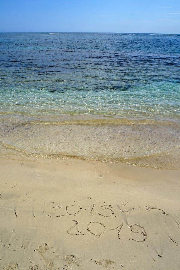 La nouvelle année numéro 2018 et 2019 dessins dans le sable sur la plage photos libres de droits