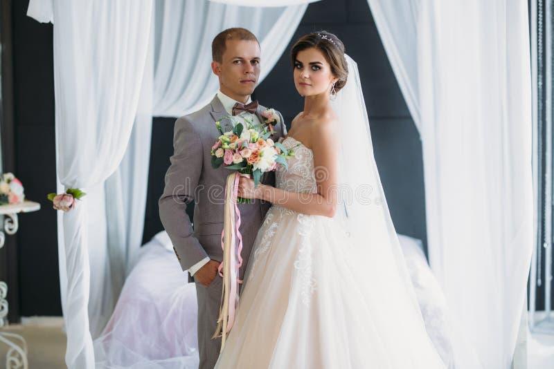 La novia abraza al novio y sostiene un ramo de flores en sus manos Un par hermoso de recienes casados en un día de boda imágenes de archivo libres de regalías