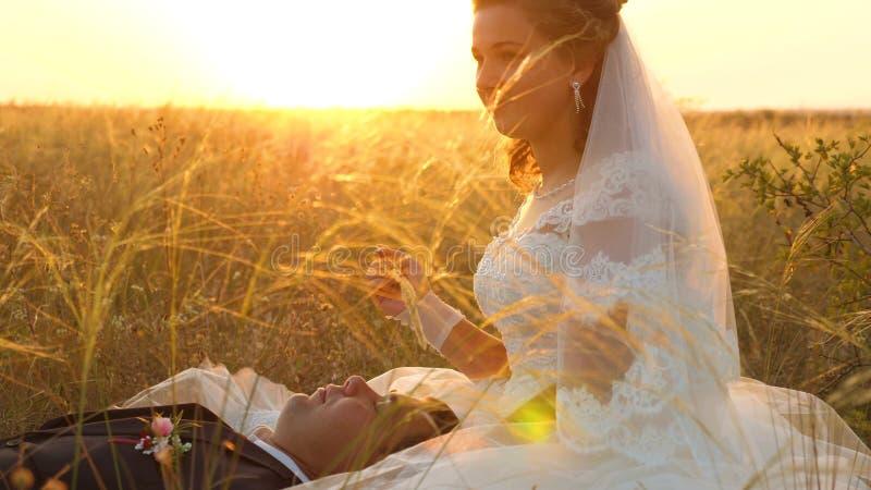 La novia acaricia al novio con el tallo de la hierba en cara la familia feliz está mintiendo en campo en rayos de la puesta del s fotografía de archivo