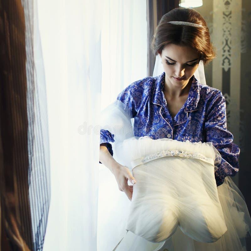 La novia ajusta un vestido de boda en el frente de la ventana imagen de archivo