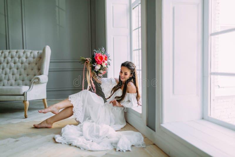 La novia alegre, joven sostiene un ramo rústico de la boda con las peonías en fondo panorámico de la ventana Retrato del primer A fotografía de archivo libre de regalías