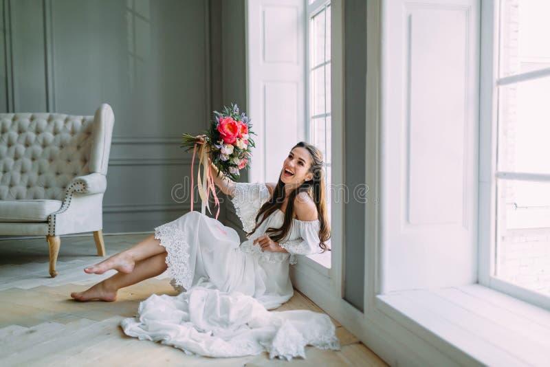 La novia alegre, joven sostiene un ramo rústico de la boda con las peonías en fondo panorámico de la ventana Retrato del primer A imágenes de archivo libres de regalías