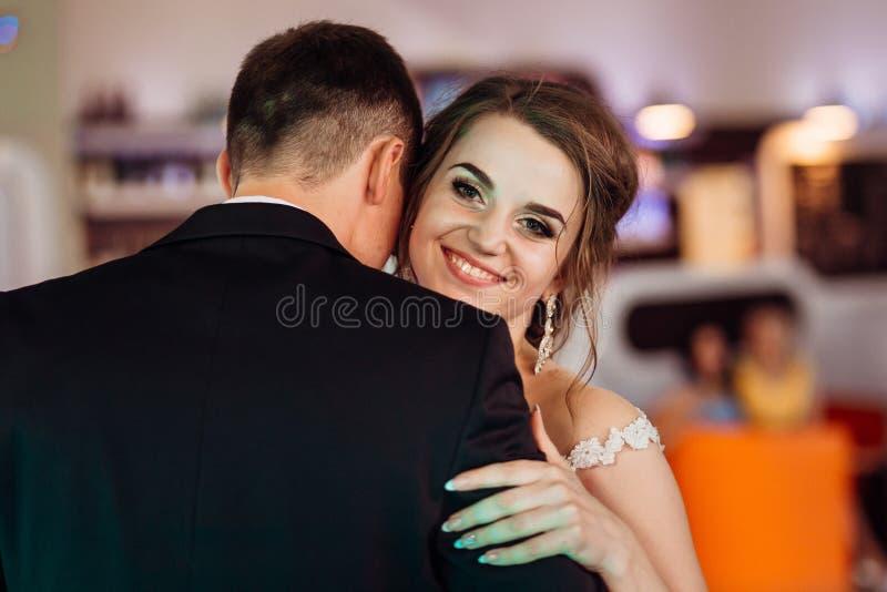 La novia alegre mira sobre el groom& x27; hombro de s mientras que baila foto de archivo