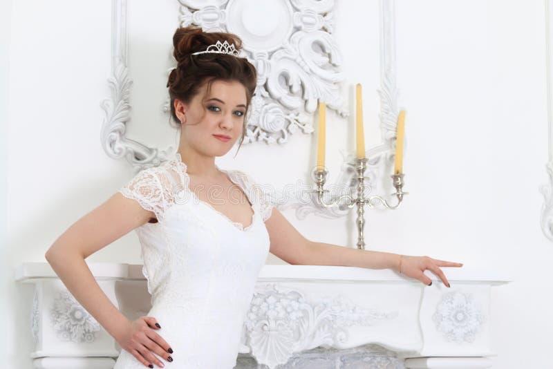 La novia bastante joven en el vestido blanco presenta cerca de cand del fireplacewith imágenes de archivo libres de regalías