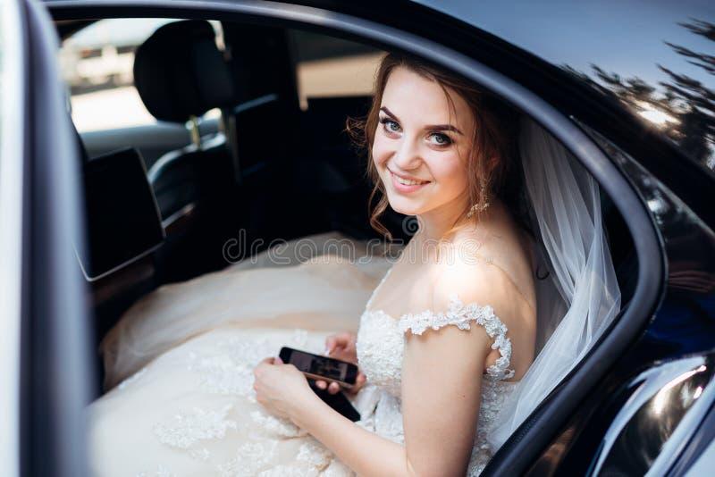 La novia bonita comprueba su teléfono mientras que se sienta en el coche fotografía de archivo libre de regalías