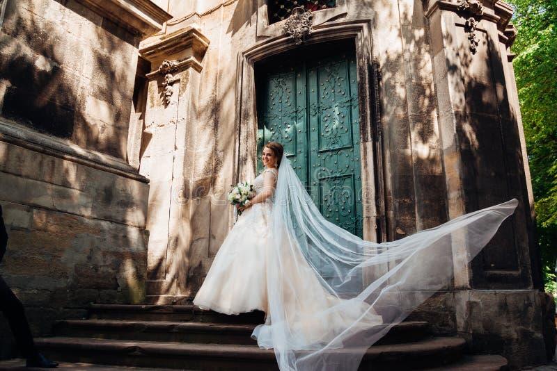 La novia bonita mira sobre su hombro mientras que el viento sopla su velo foto de archivo libre de regalías