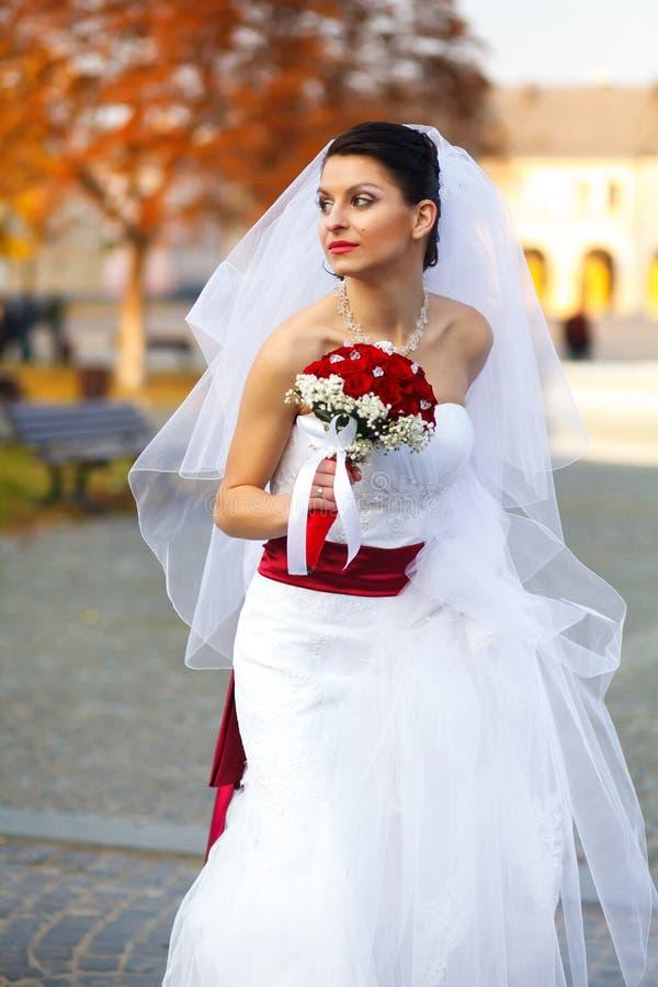 La novia camina alrededor de una ciudad del otoño que sostiene una falda del dre de la boda fotografía de archivo libre de regalías