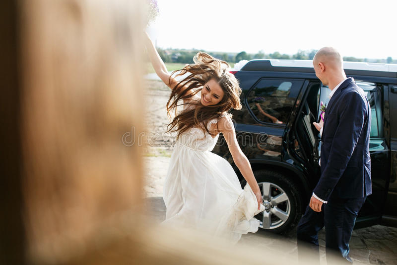 La novia camina baile en la luz del sol mientras que el novio cierra un beh del coche fotos de archivo