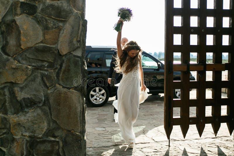 La novia camina como un ganador en las puertas de madera grandes que llevan a cabo su bouque foto de archivo