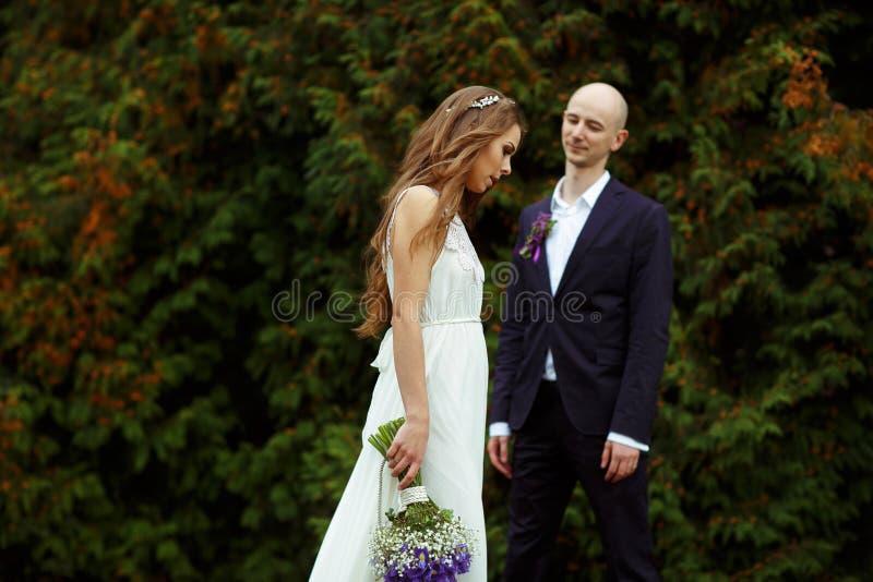 La novia con un ramo de azafranes violetas camina detrás de un novio fotografía de archivo libre de regalías