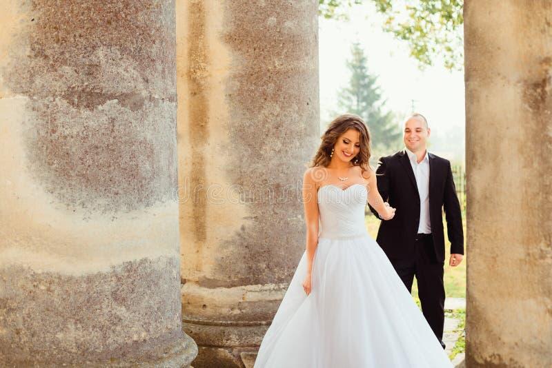 La novia de deslumbramiento lleva a su hombre entre pilares viejos imagen de archivo