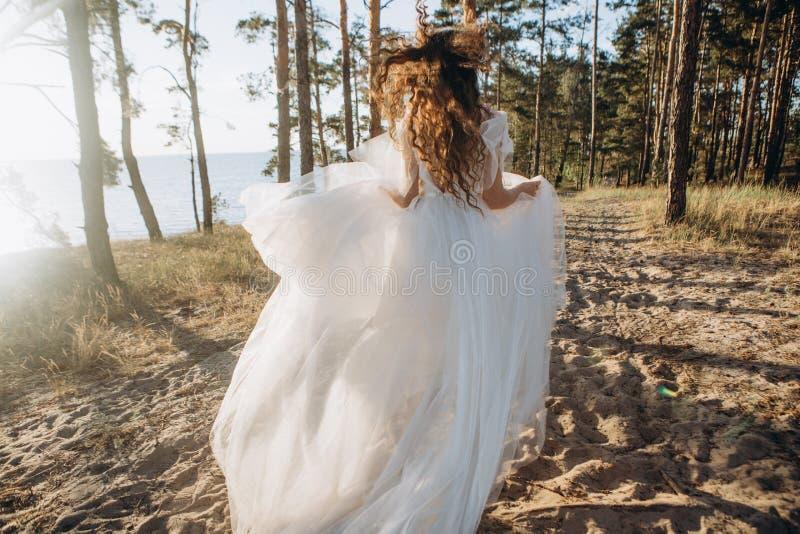 La novia de la muchacha corre los árboles de la arena que pasan por alto el mar imagen de archivo libre de regalías