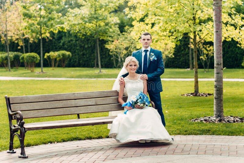 La novia de pelo rubio joven se sienta en un banco al lado del novio en un parque exótico imágenes de archivo libres de regalías