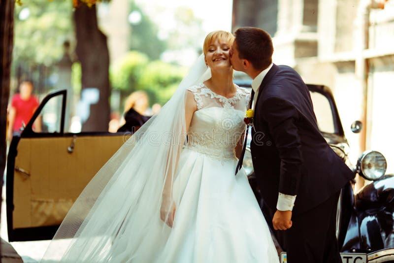 La novia disfruta del beso del novio que se coloca en el frente de un coche viejo imagenes de archivo