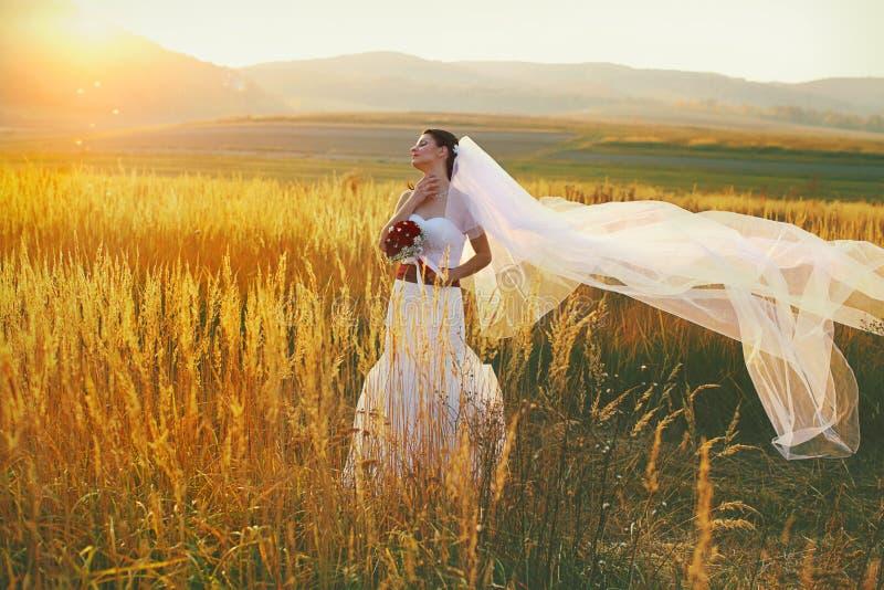 La novia disfruta del viento y de la sol que se colocan en el campo imagenes de archivo