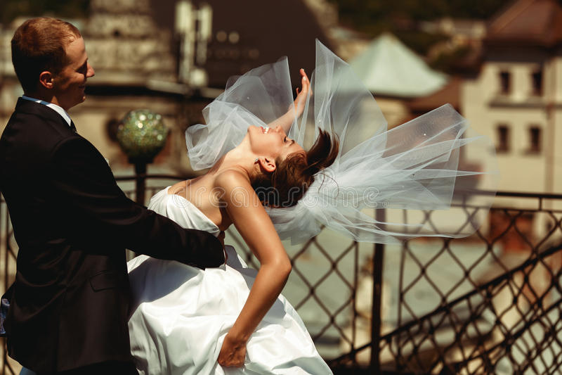La novia dobla encima en manos del ` s del novio y su velo se separa alrededor fotos de archivo