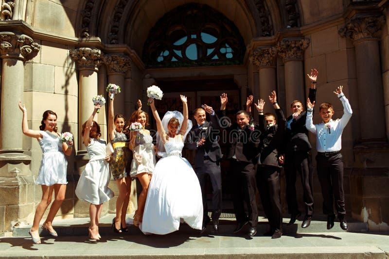 La novia, el novio y los amigos saltan en el frente de una puerta grande del fotografía de archivo