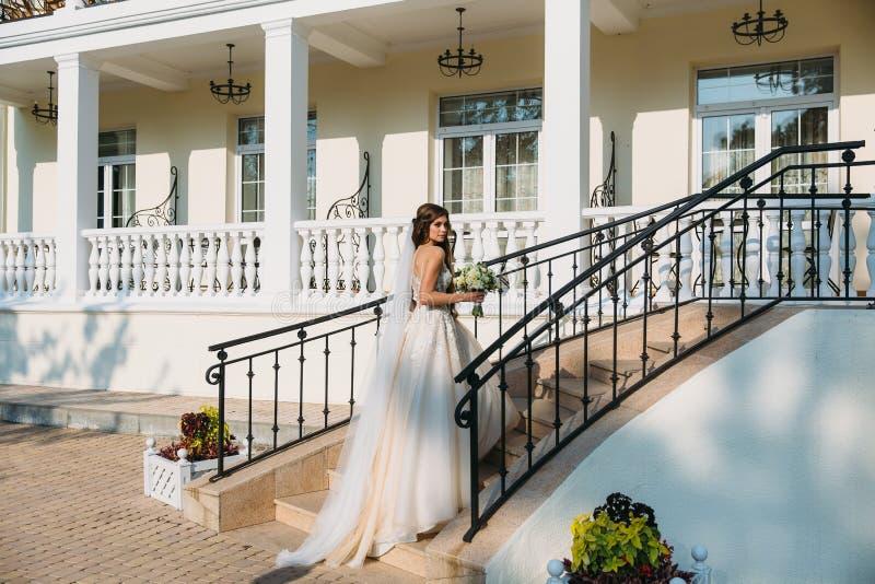 La novia elegante con la boda florece el ramo, mujer atractiva en vestido de boda La chica joven en un vestido blanco va fotografía de archivo libre de regalías