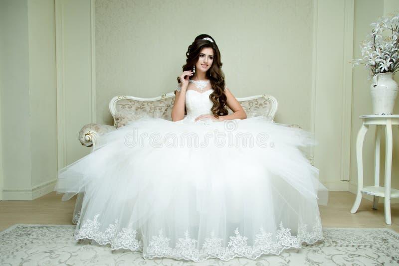 La novia elegante morena hermosa con maquillaje de la boda y el peinado con el diamante coronan sentarse en butaca del vintage fotos de archivo libres de regalías
