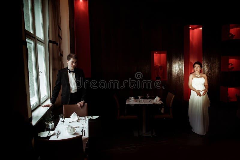 La novia embarazada camina en el café al novio que la espera imagenes de archivo
