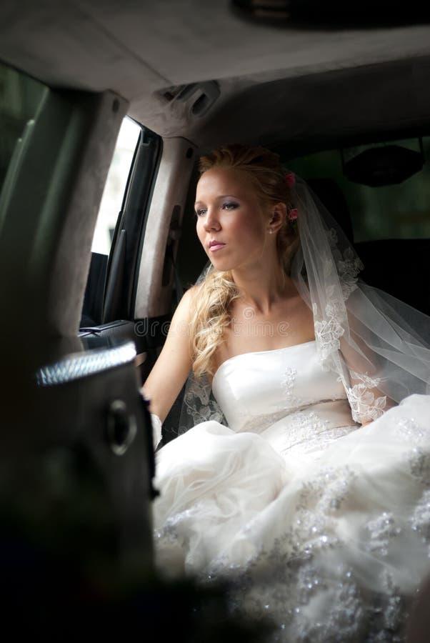 La novia en alineada de boda se sienta en limusina fotos de archivo